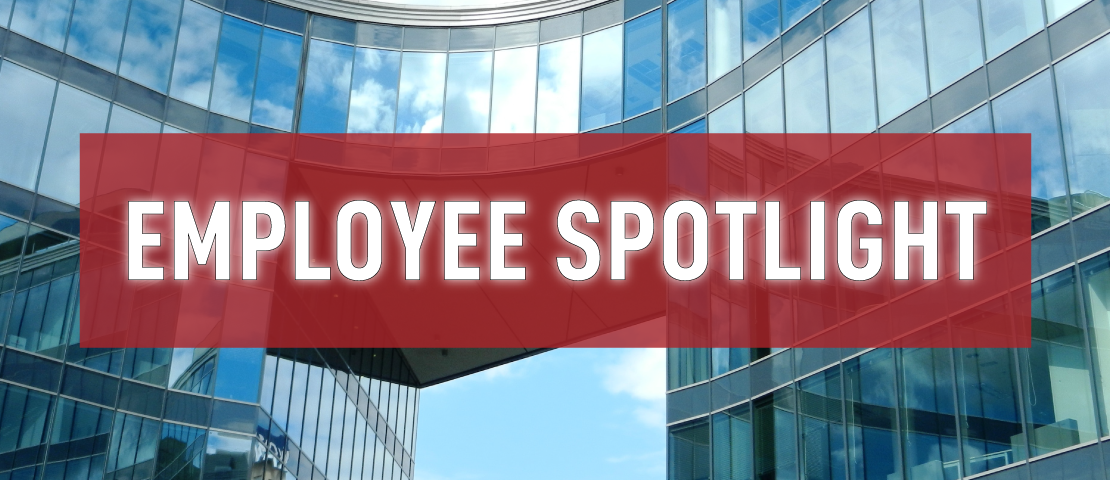 """A picture of an office building with text overlapping. The text says """"Employee Spotlight."""""""